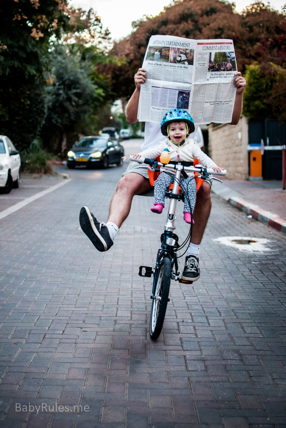 Baby riding bike while father reading newspaper