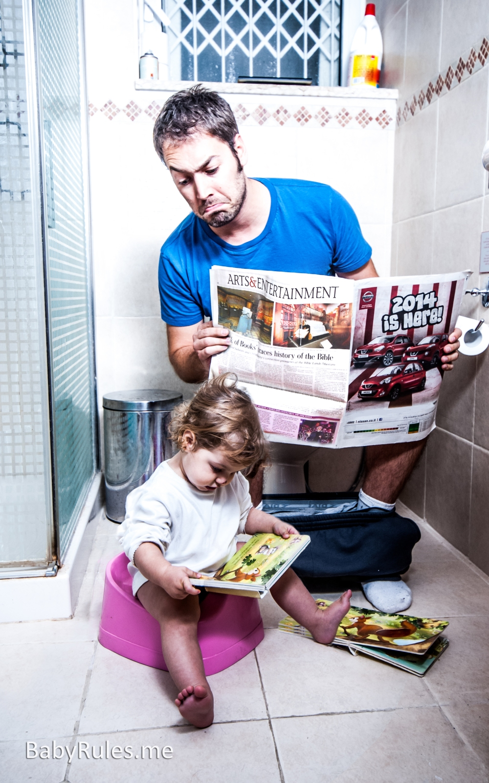 father and daughter in toilet reading newspaper